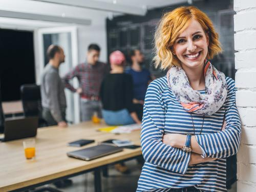 Photo of young business woman in a conference room, with a group of coworkers in backside