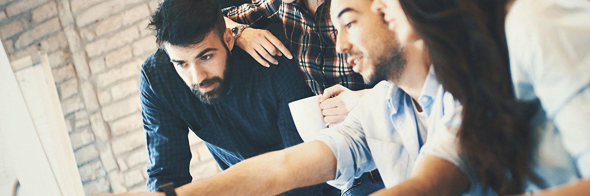 Closeup side view of group of IT experts completing a task in their office. There are two men and two women gathered around dual screen computer. One of the men is leading the project.