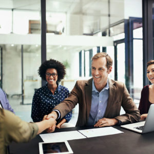 Shot of colleagues shaking hands during a meeting at work